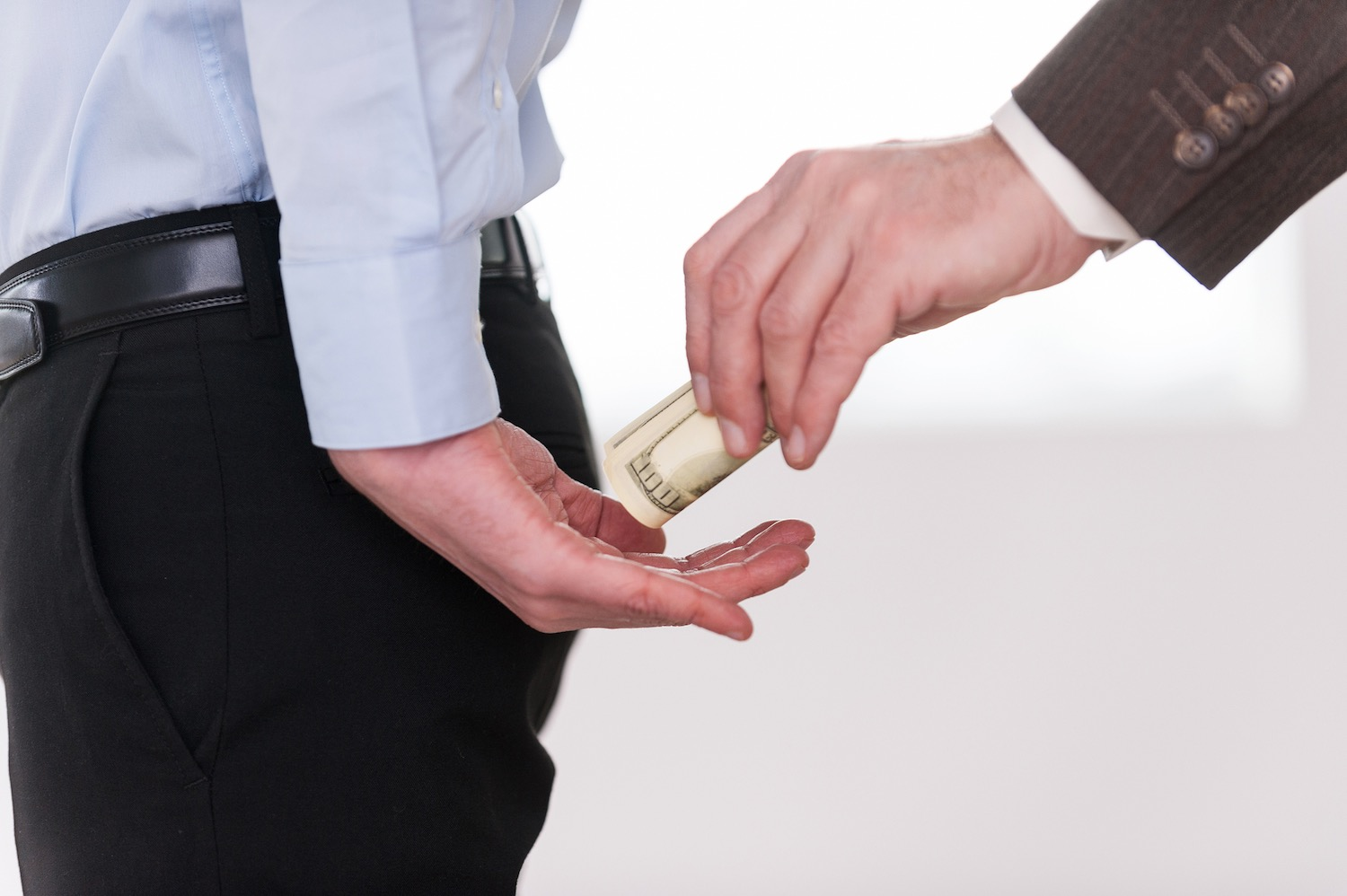 Close-up of businessman giving money to another man in formalwear