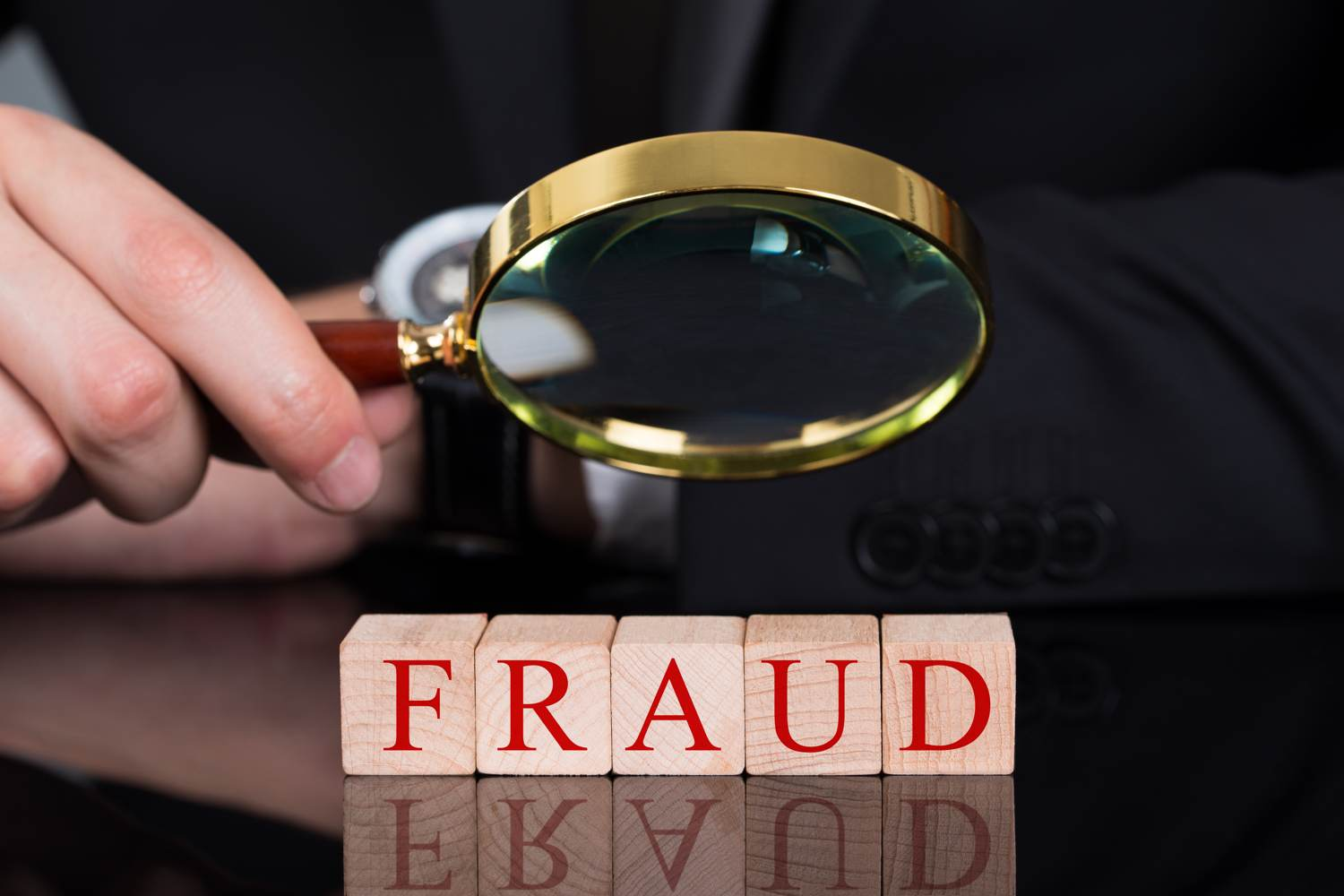 Fraud in the UK - Man holding magnifying glass over wooden blocks that spell out 'fraud'.