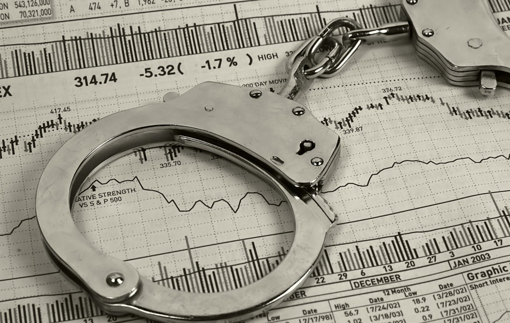 Photo of Handcuffs and Stock Charts.