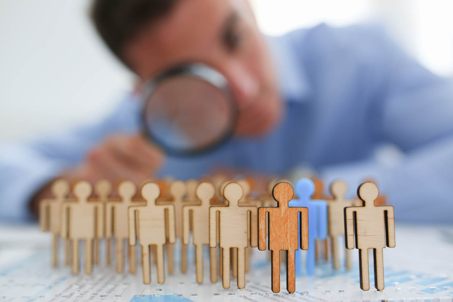 Searching for person concept - out of focus man uses magnifying glass oto look at little e wooden statuettes of people. One of them is blue.